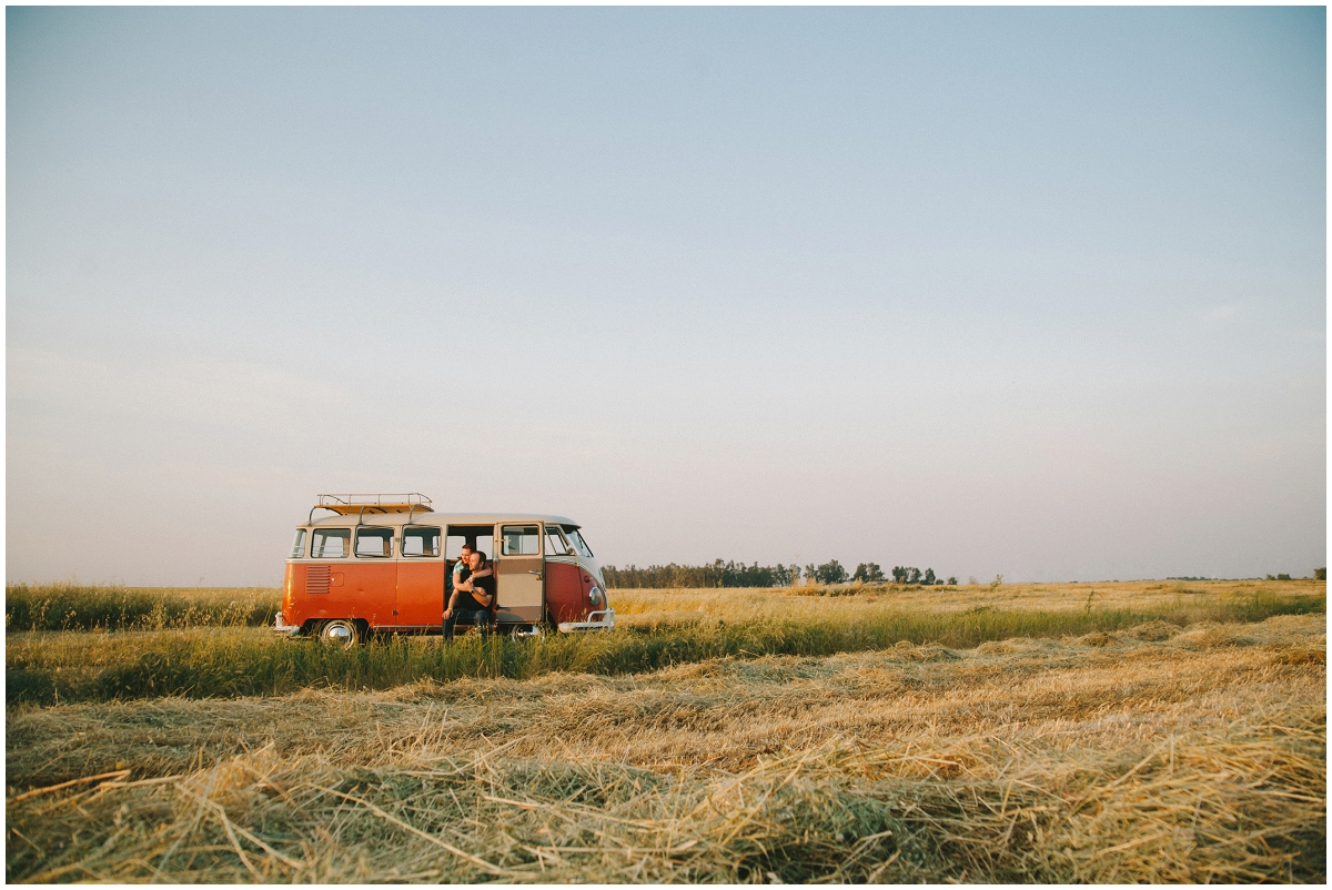 Romantic Red VW bus engagement photo in a field
