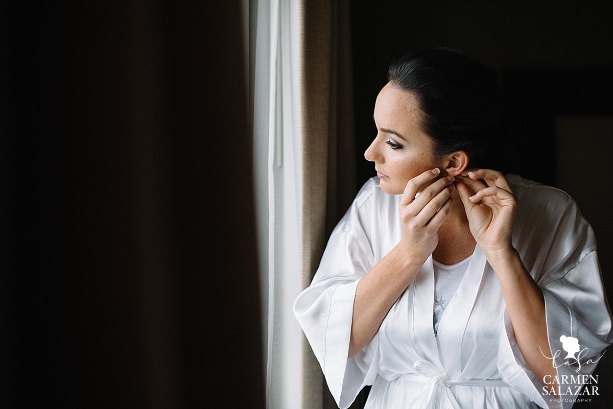 Glowing bride putting on jewelry - Carmen Salazar