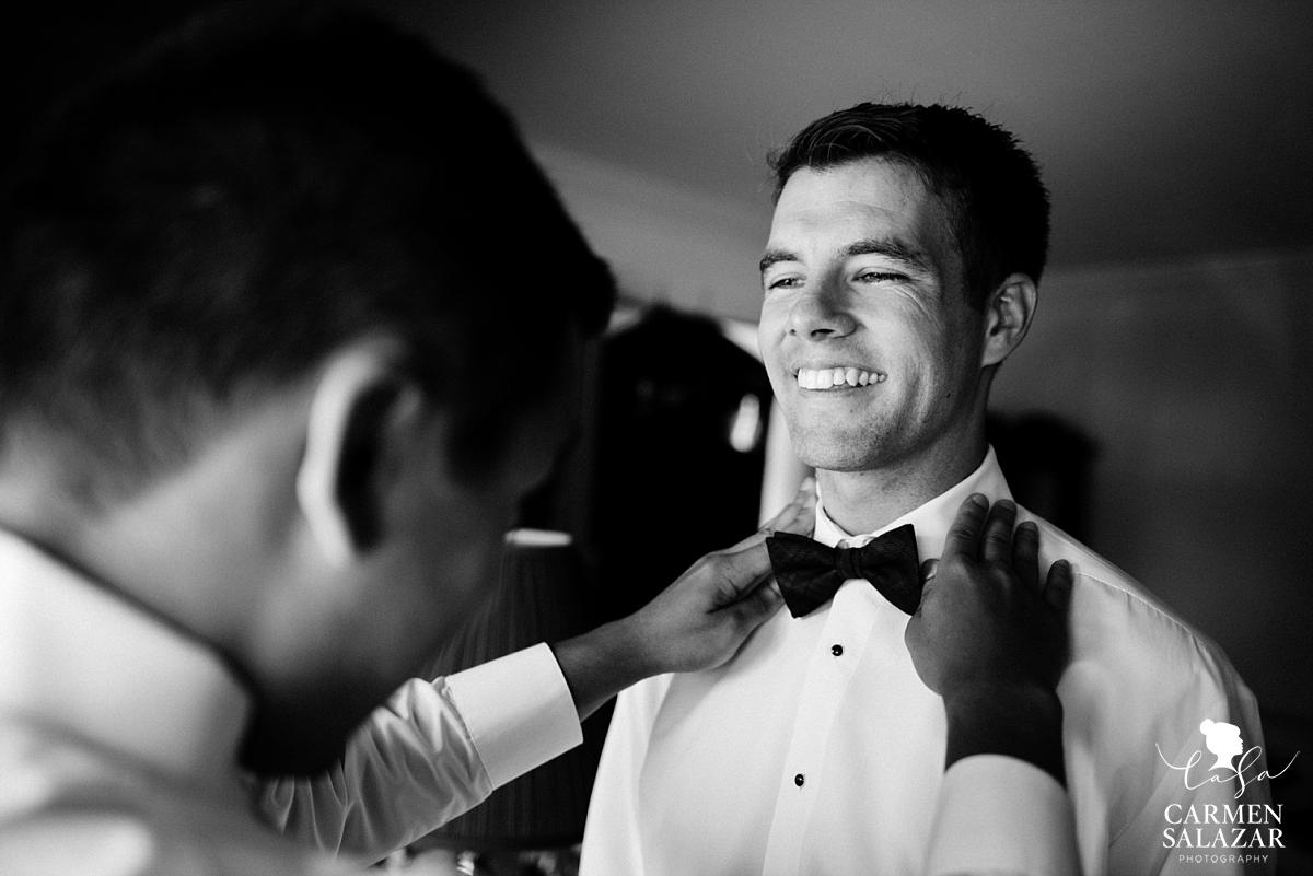 Classic groom putting on bowtie - Carmen Salazar