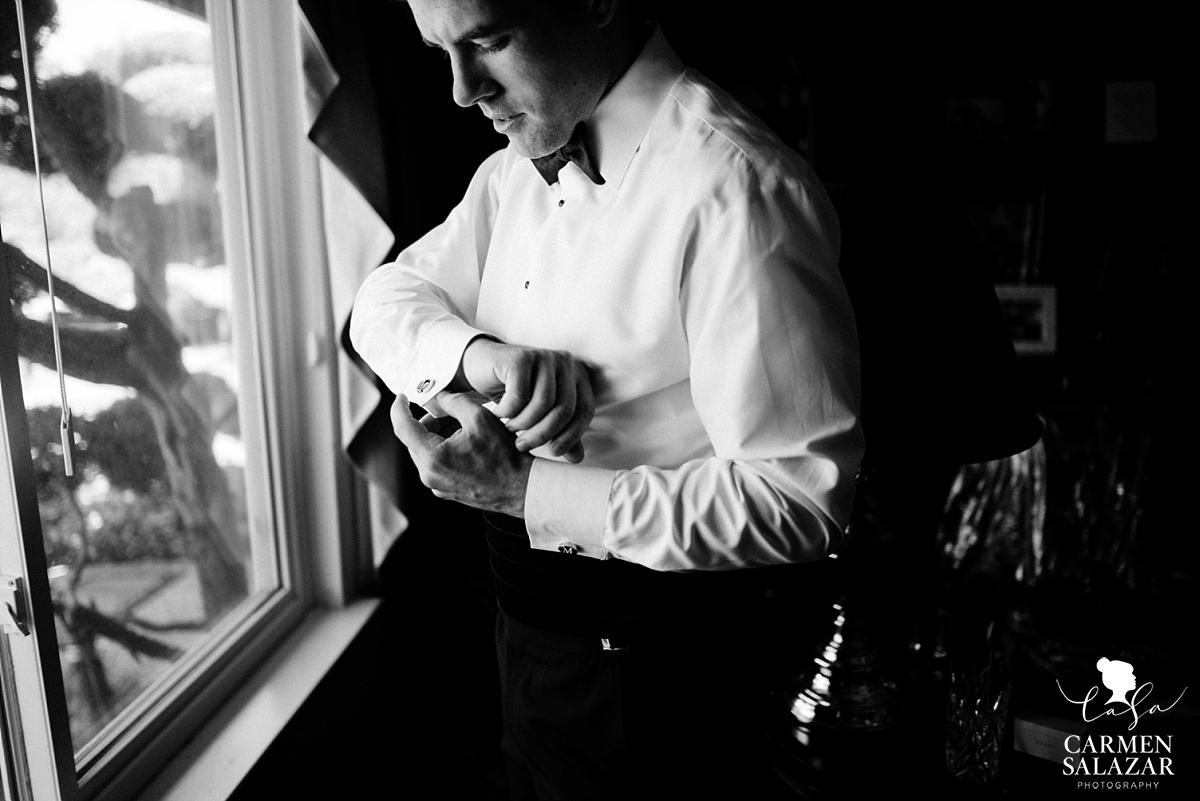 Dashing groom putting on cufflinks - Carmen Salazar