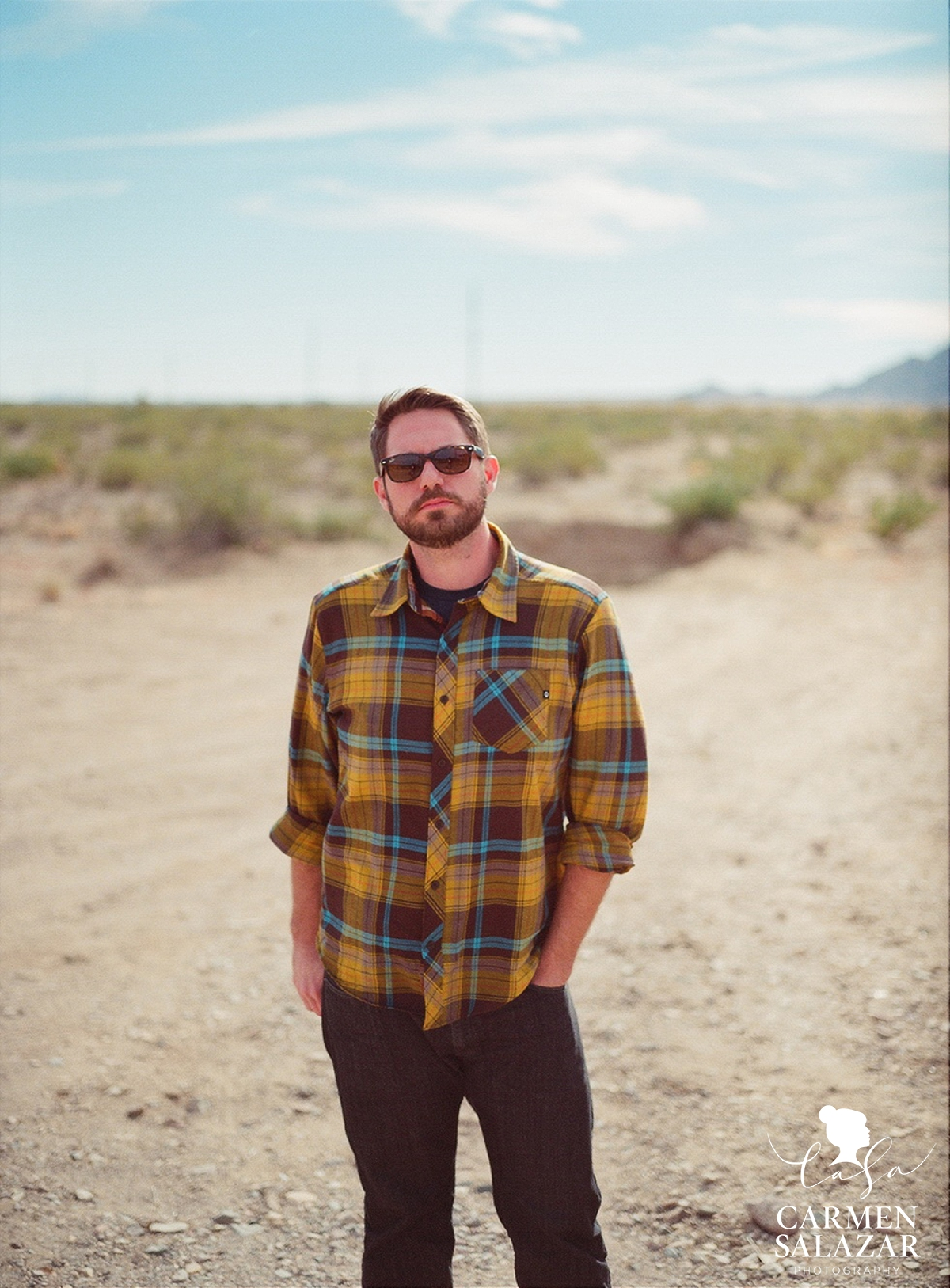 portrait of bearded man in flannel shirt in the desert by Carmen Salazar Photography