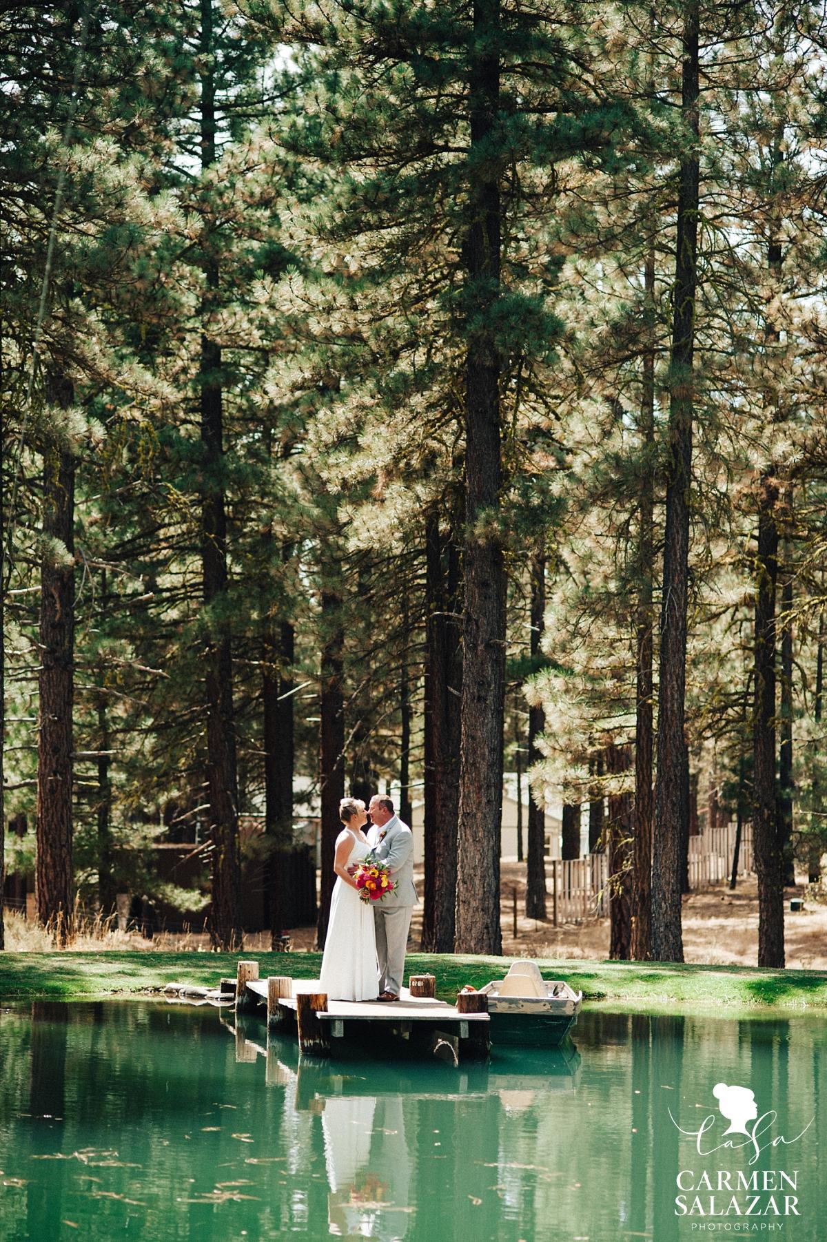 Bride and groom on dock at a pond - Carmen Salazar