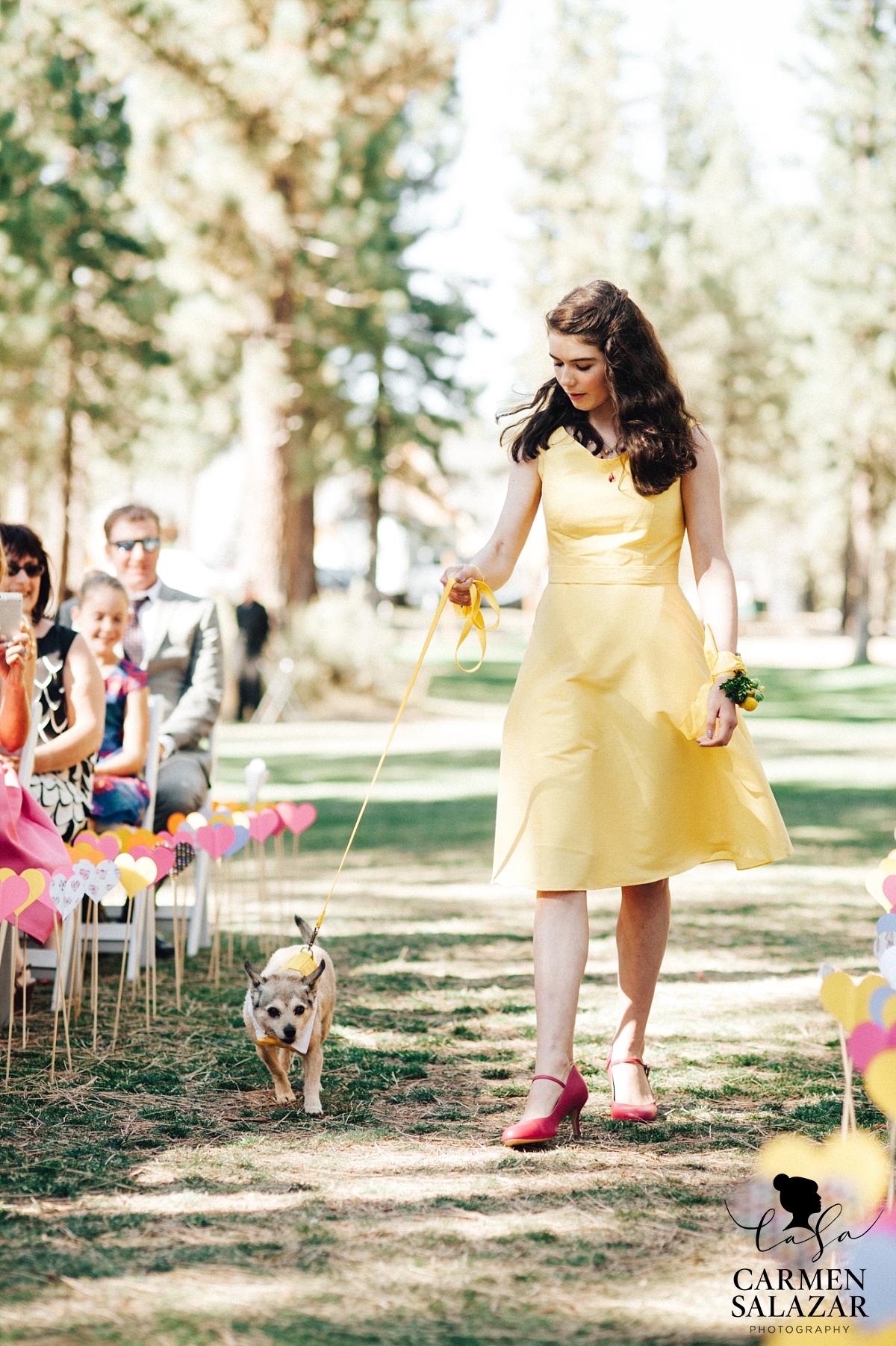 Bright junior bridesmaid walking dog down wedding aisle - Carmen Salazar