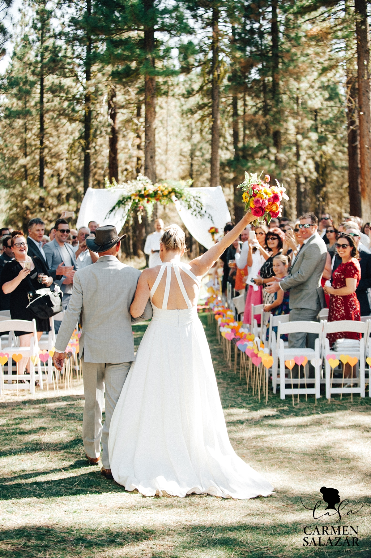 Excited bride walking down the aisle at Chalet View Lodge wedding - Carmen Salazar