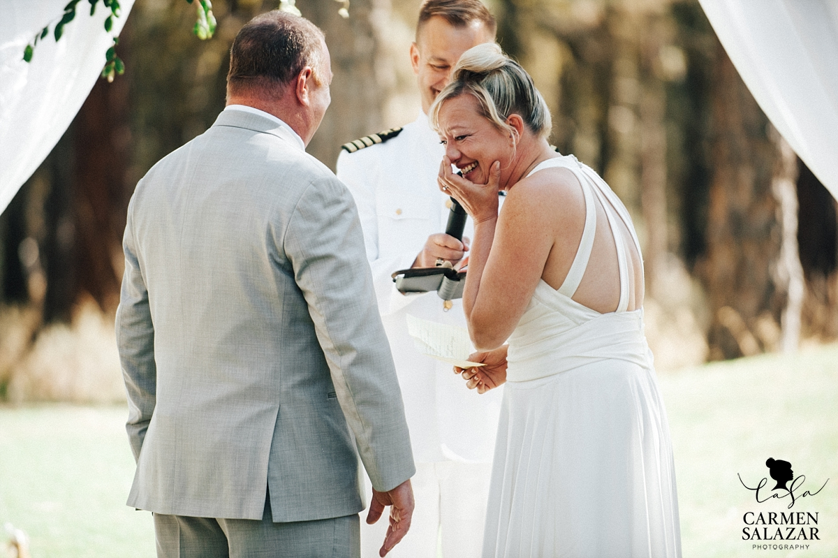 Laughing bride at outdoor ceremony - Carmen Salazar