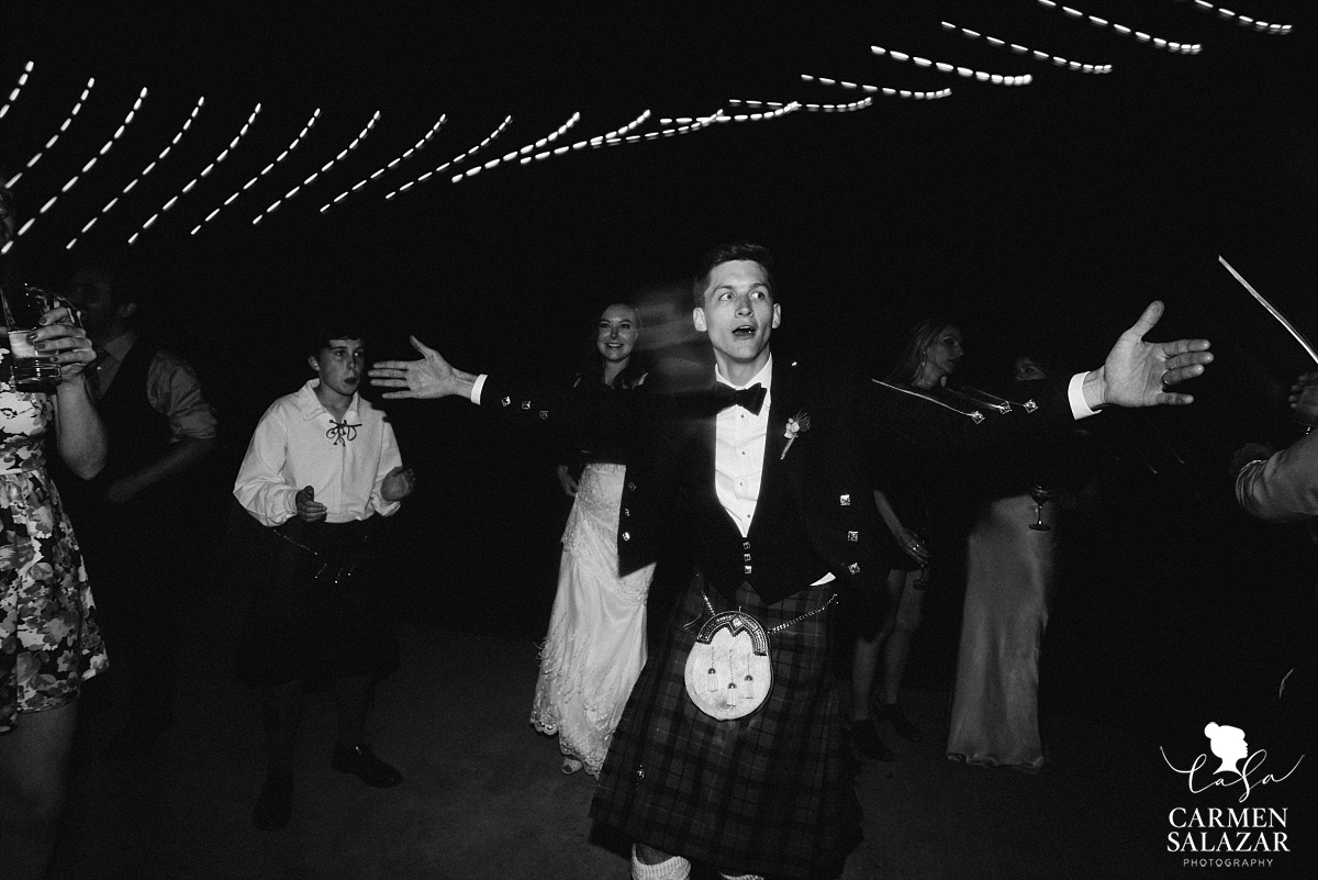 Groom doing a silly dance at outdoor reception - Carmen Salazar