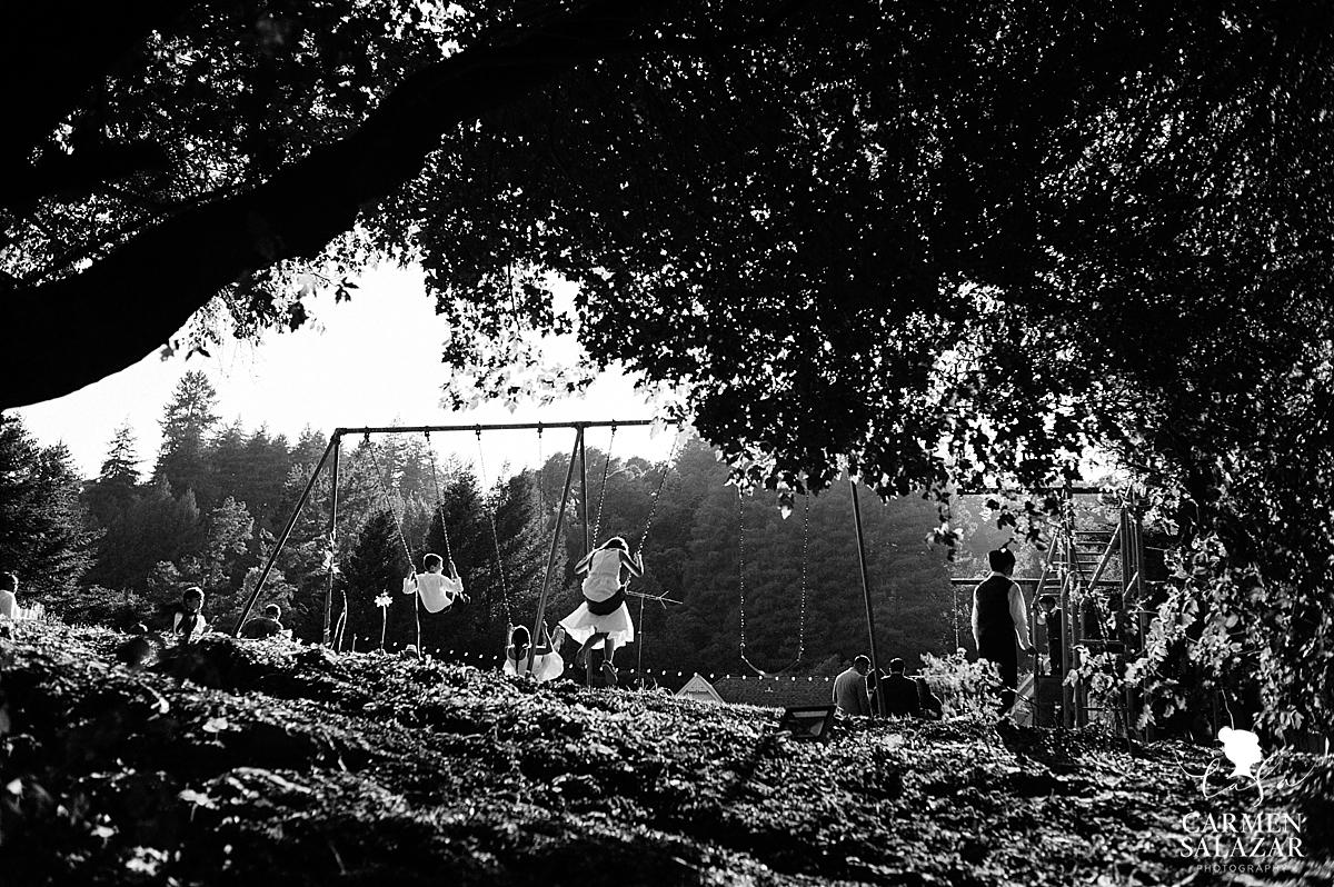 Kids swinging on wedding playground - Carmen Salazar