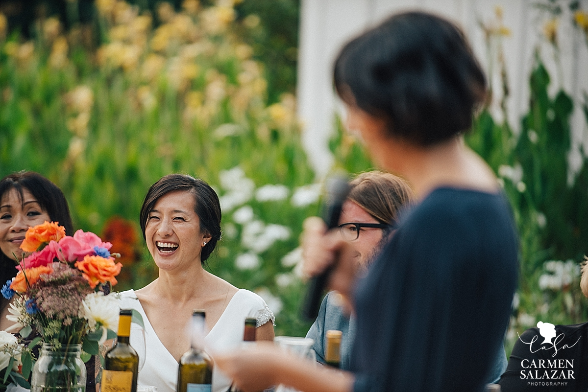 laughing bride during wedding toast and speech by Maid of honor - Carmen Salazar