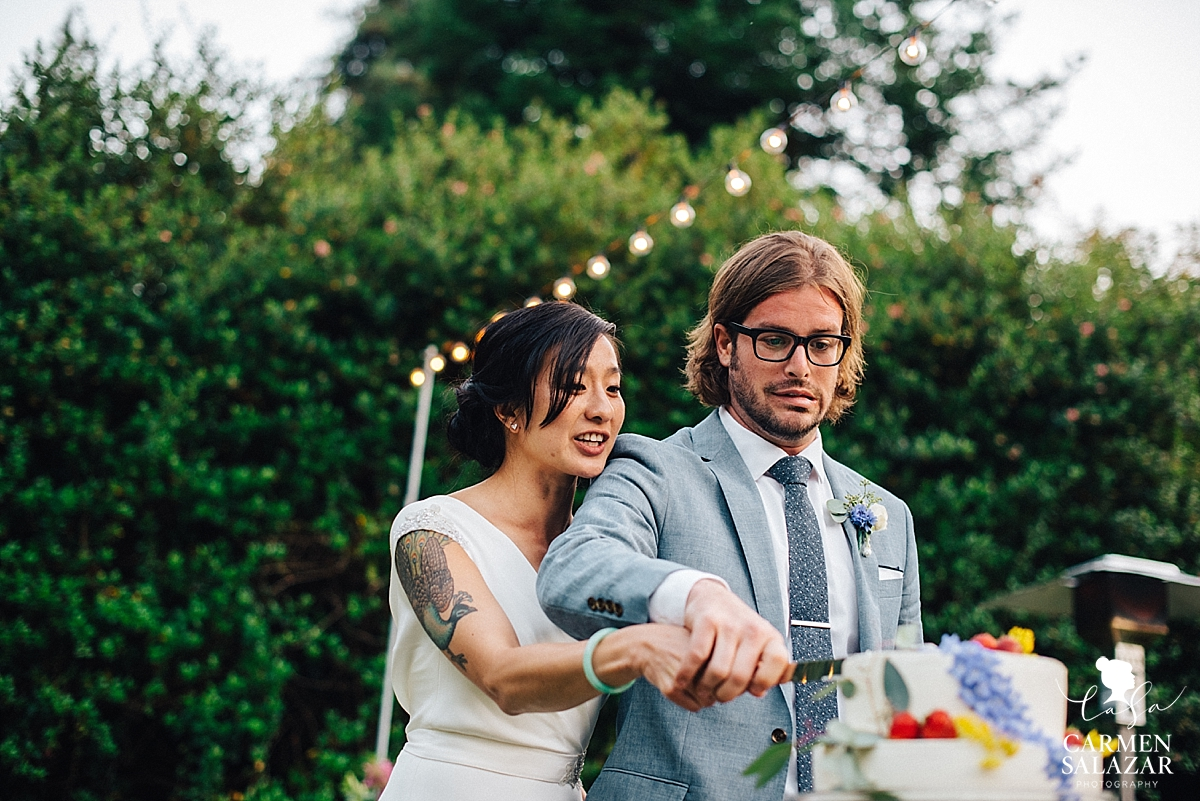 nervous Groom making silly face while cutting cake - Carmen Salazar