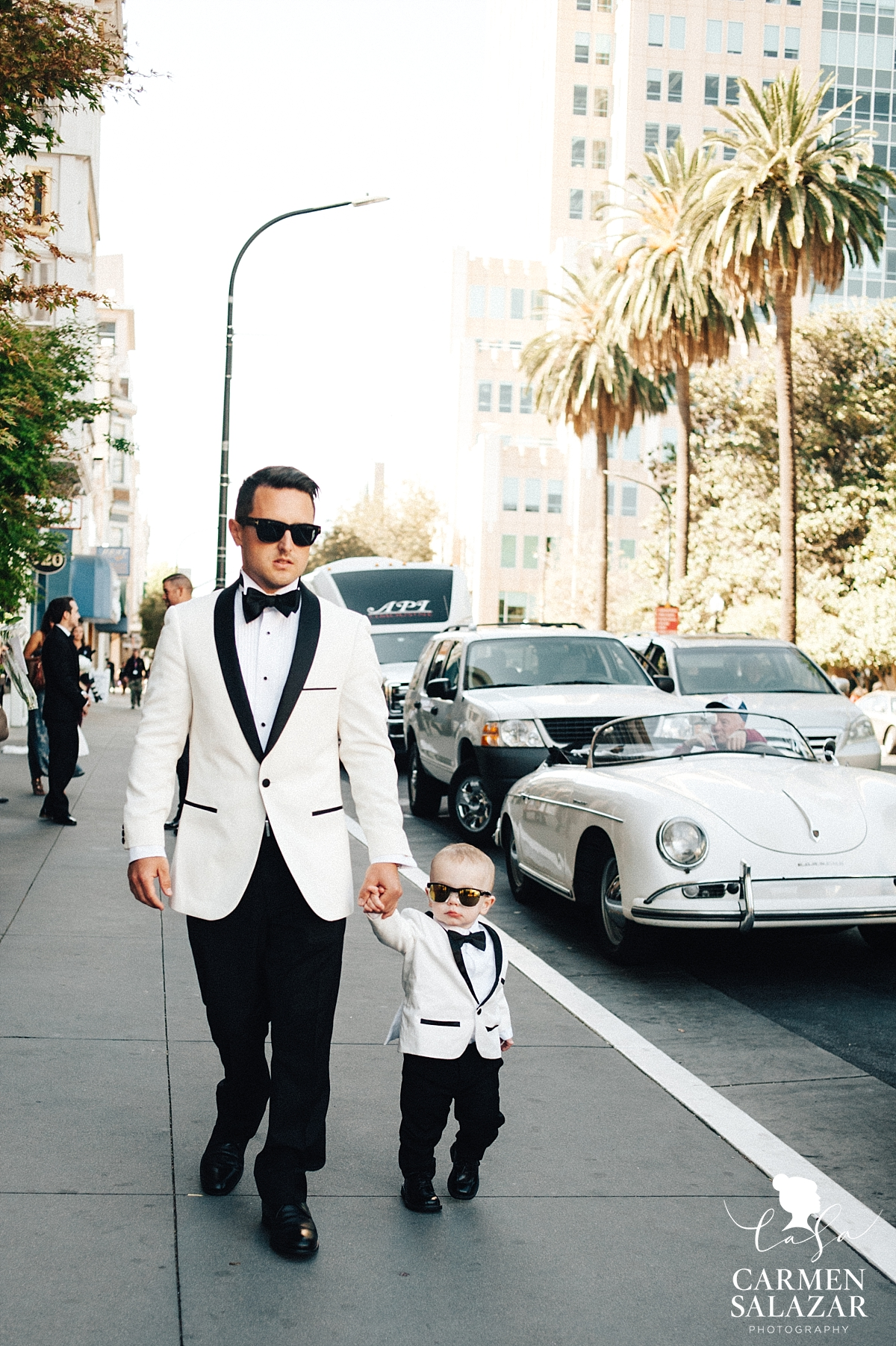 Cool groom and toddler son walking to wedding - Carmen Salazar