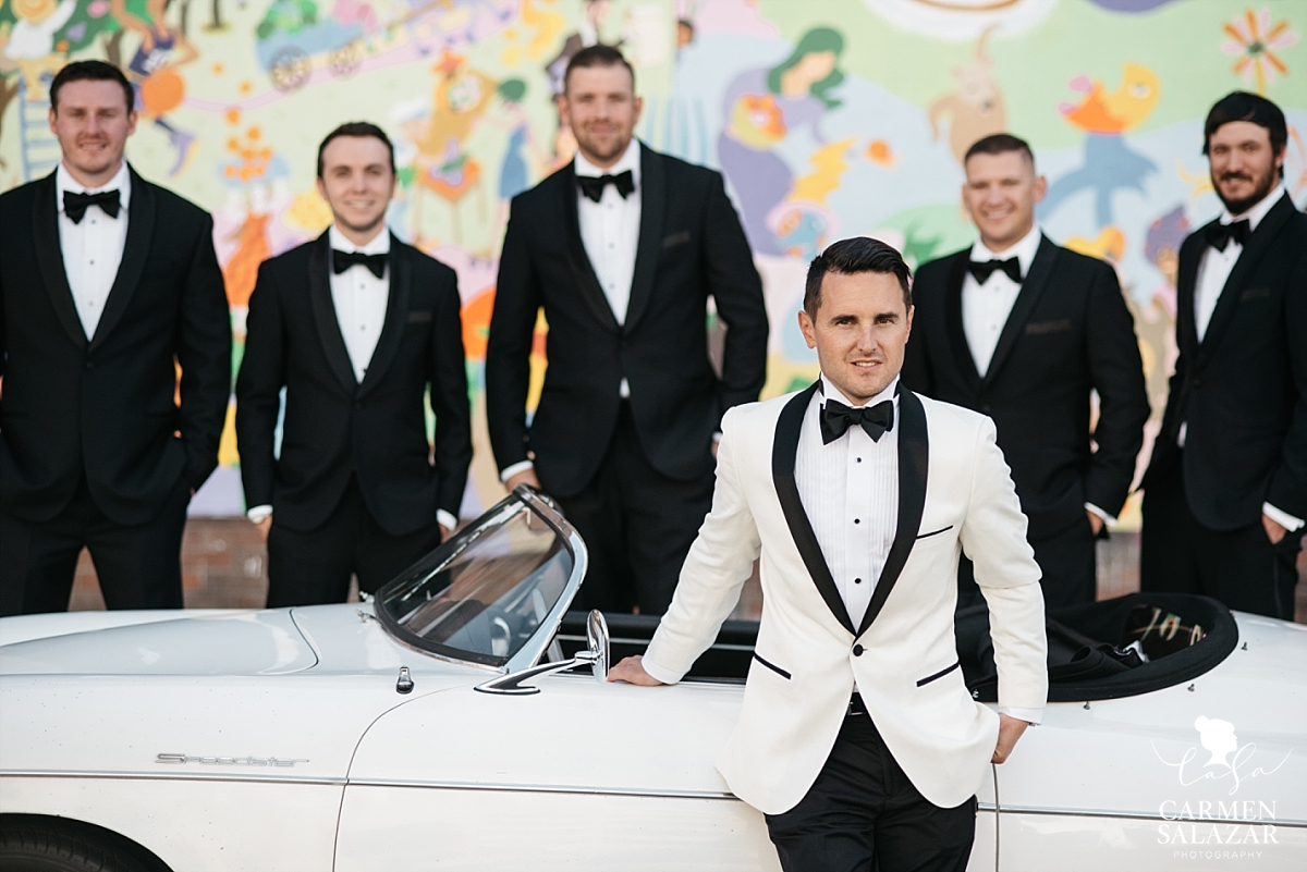Groom and groomsmen posing with vintage Porsche - Carmen Salazar