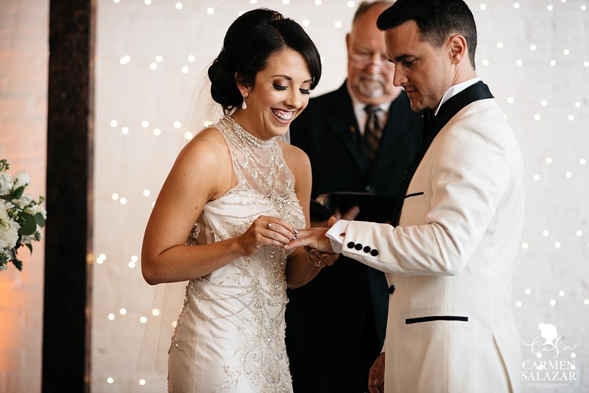 Bride putting ring on groom's finger at The Find - Carmen Salazar