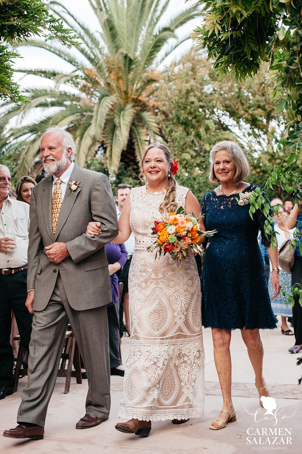 Beaming Winters bride walking the aisle with both parents - Carmen Salazar