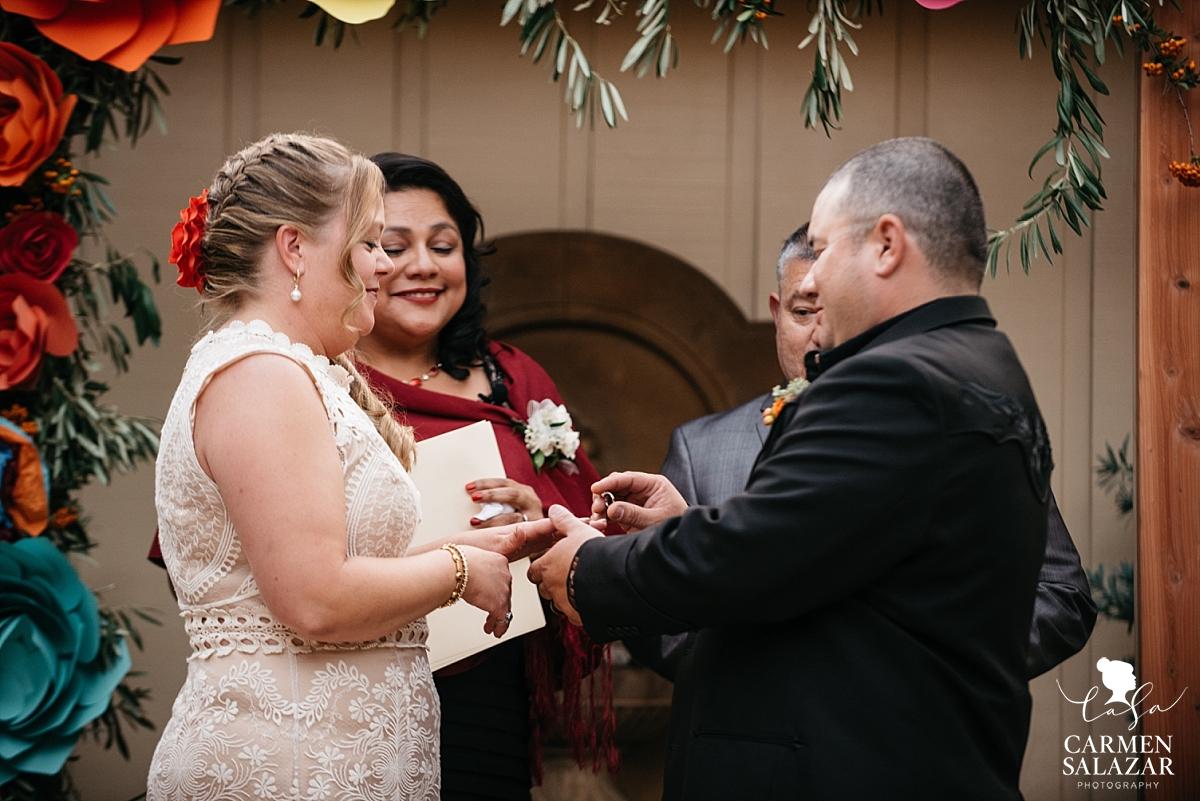 Groom puts ring on bride at Winters private estate wedding - Carmen Salazar