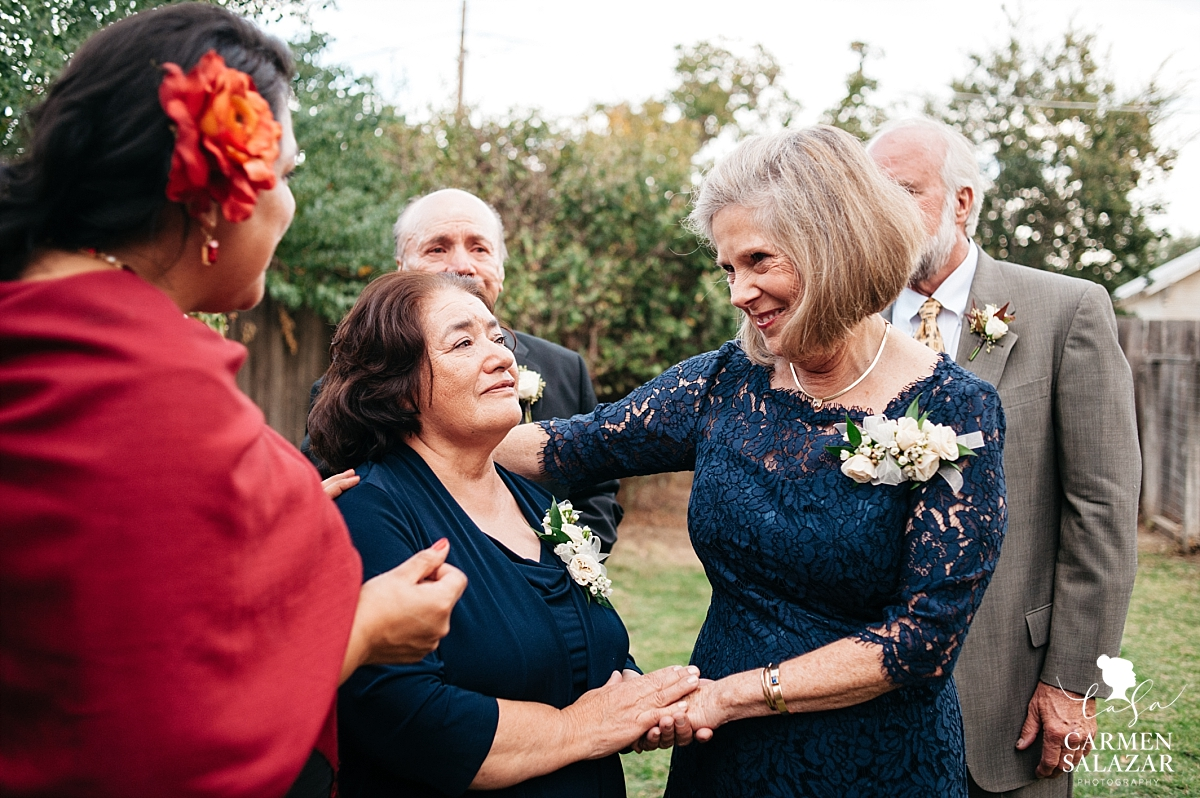 In-laws embracing after backyard wedding ceremony - Carmen Salazar