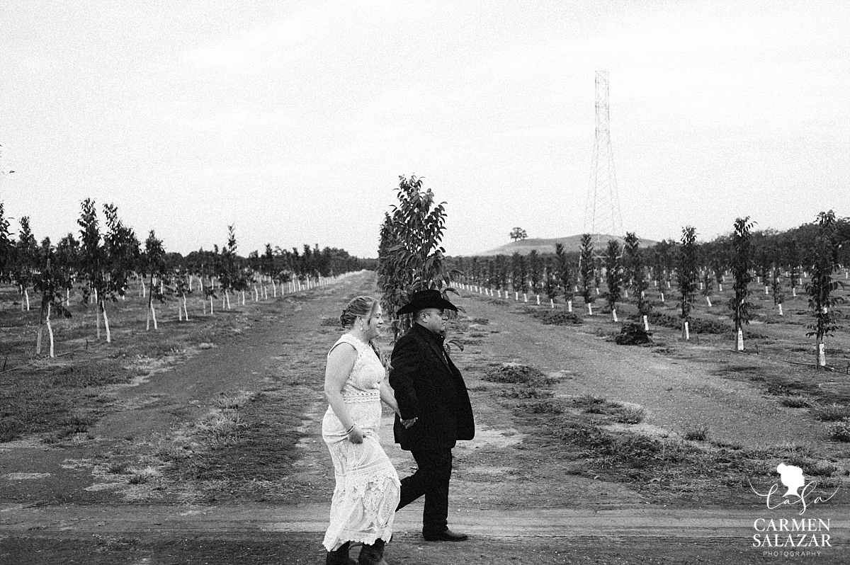 Bride and groom walking along orchards to reception - Carmen Salazar