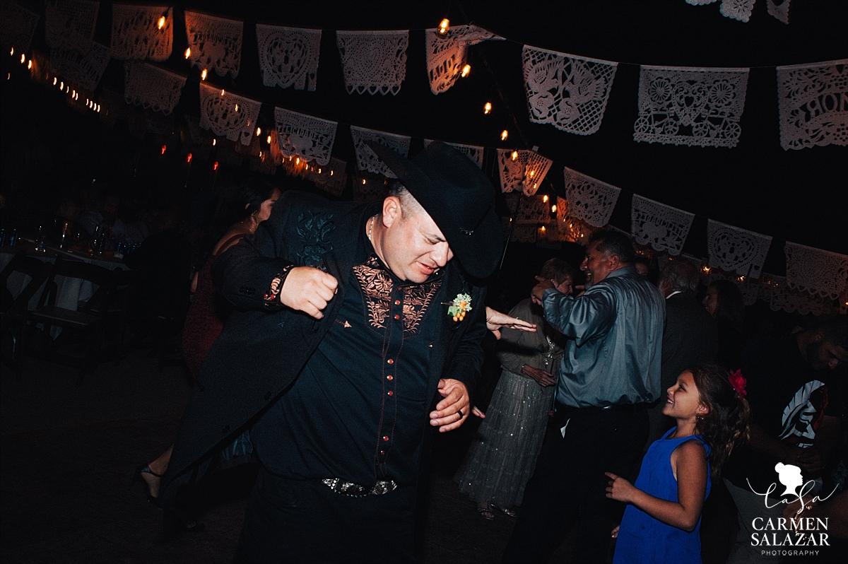 Cowyboy groom dancing at outdoor reception - Carmen Salazar