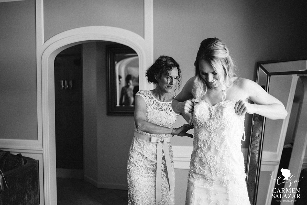 Mother helps bride put on gown - Carmen Salazar
