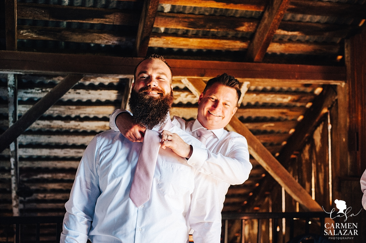 Happy groomsmen getting ready in barn - Carmen Salazar