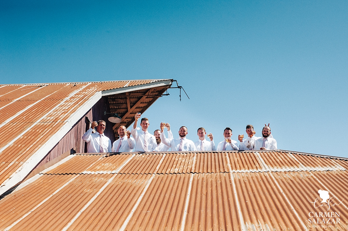 Groomsmen toasting on vintage barn roof - Carmen Salazar