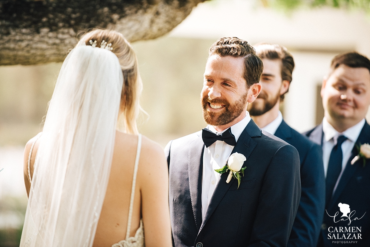 Groom looking lovingly at his bride during vows - Carmen Salazar