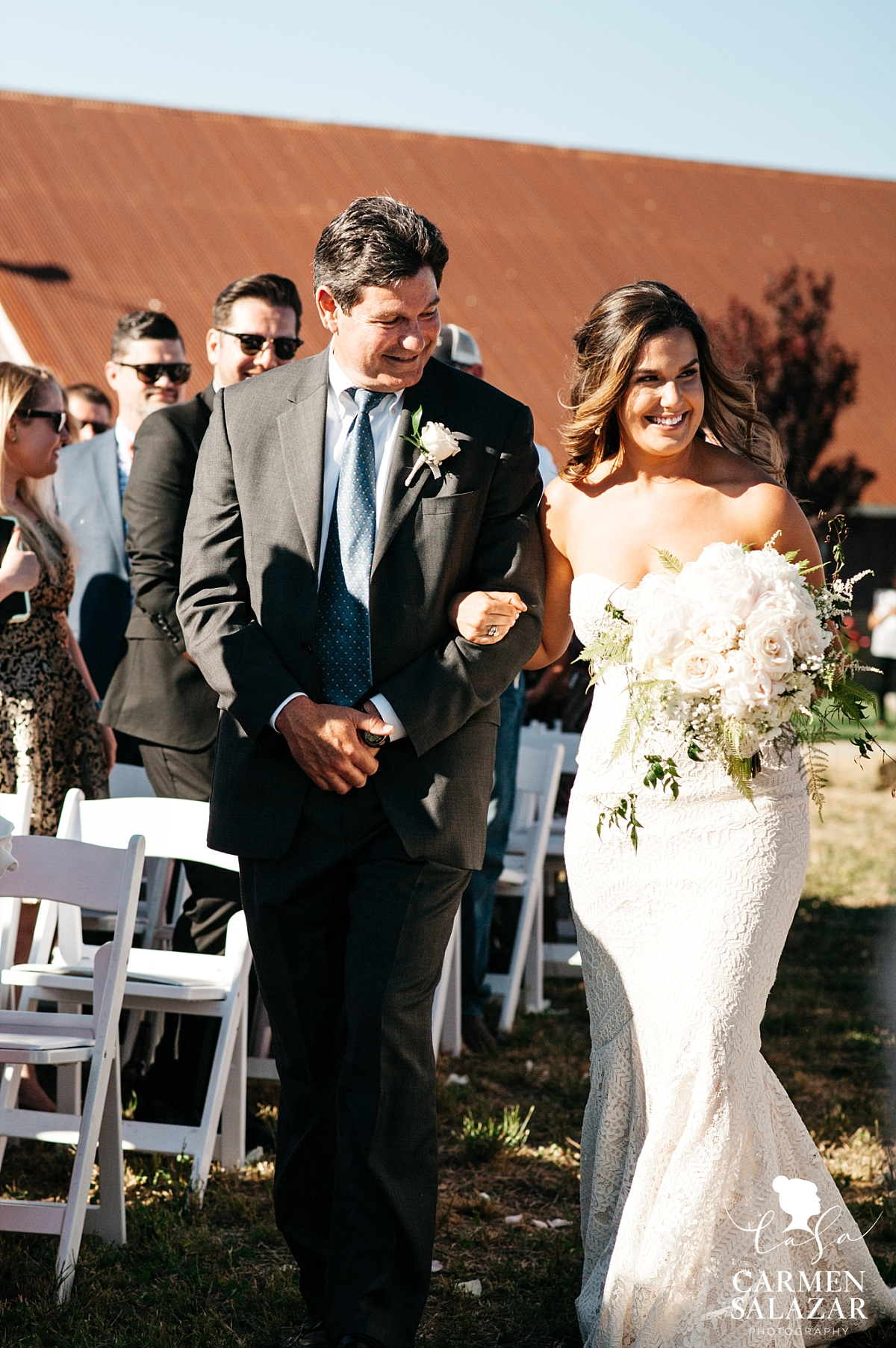 Barn wedding bride walks the aisle - Carmen Salazar