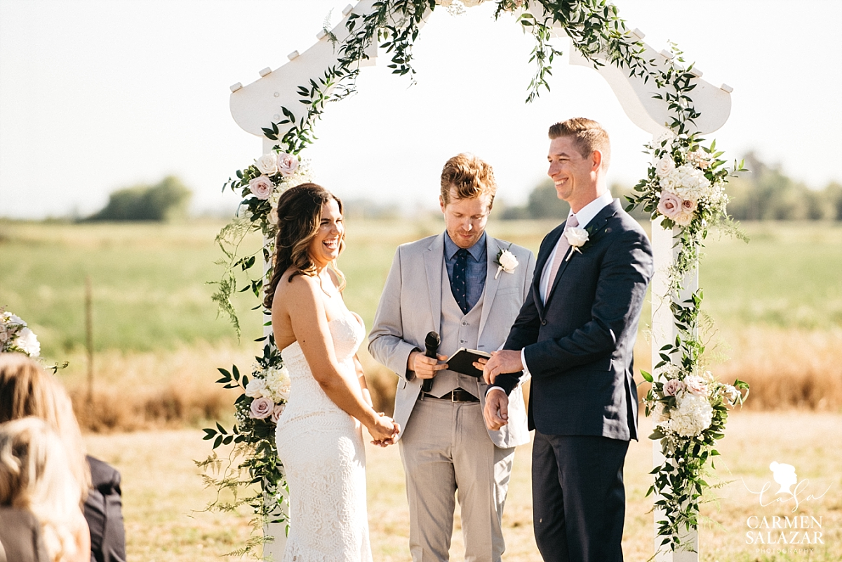 Giggling bride and groom at outdoor ceremony - Carmen Salazar