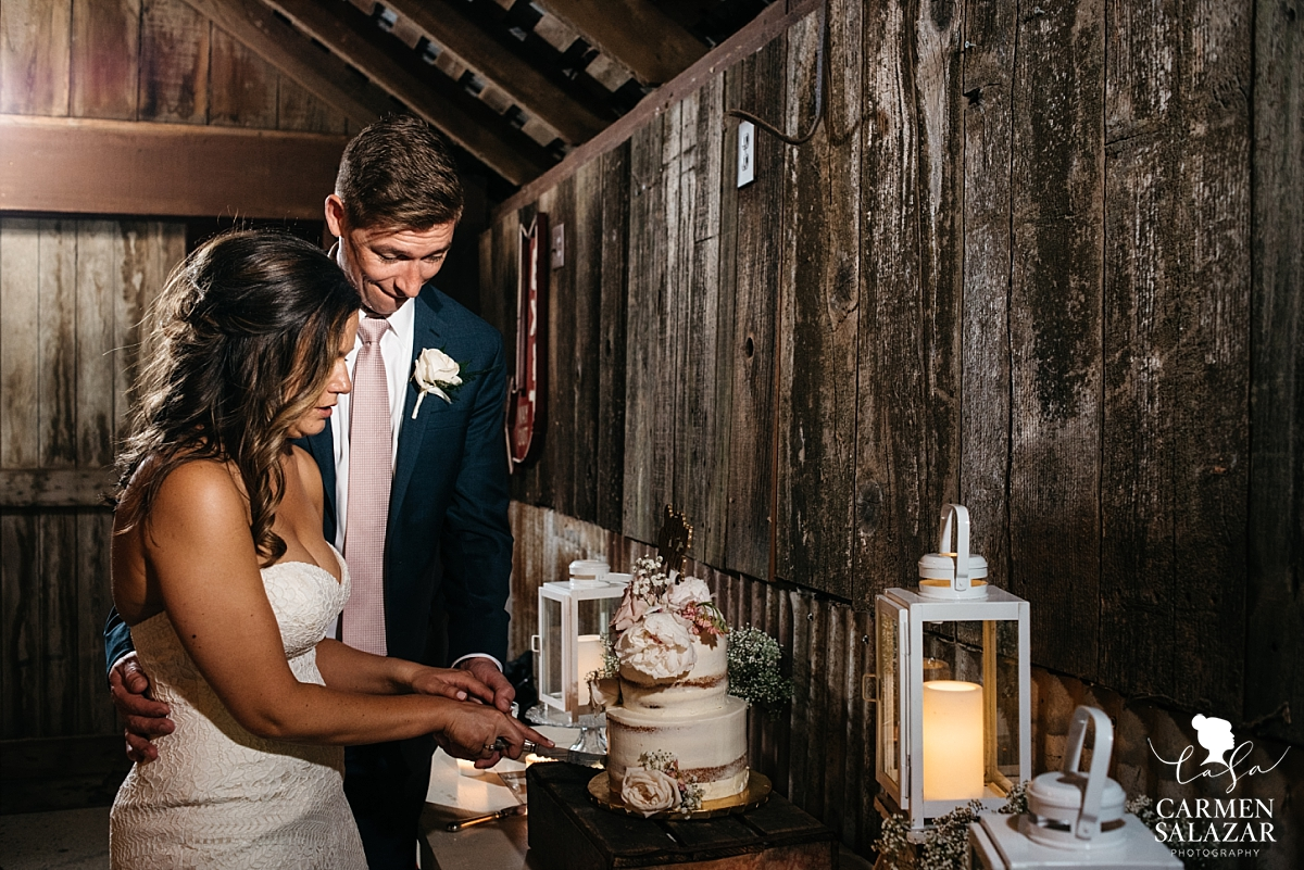 Bride and groom cutting cake in rustic barn - Carmen Salazar