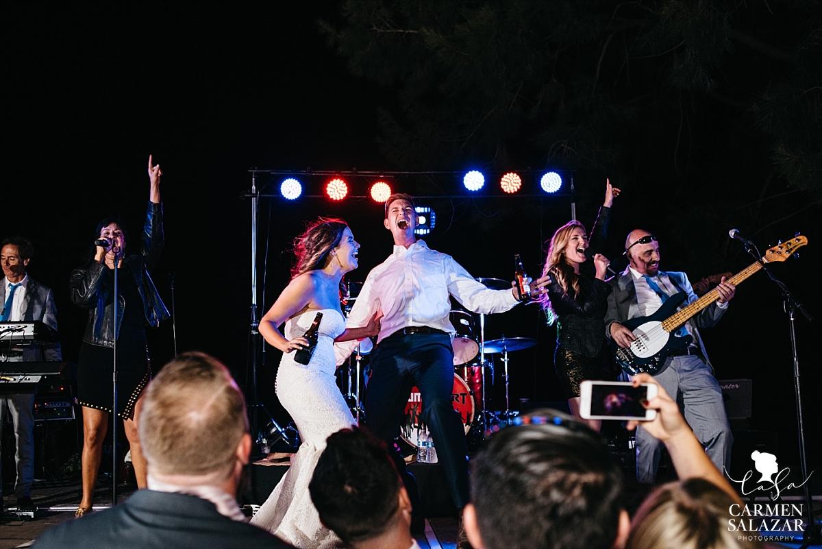 Bride and groom singing Journey onstage - Carmen Salazar