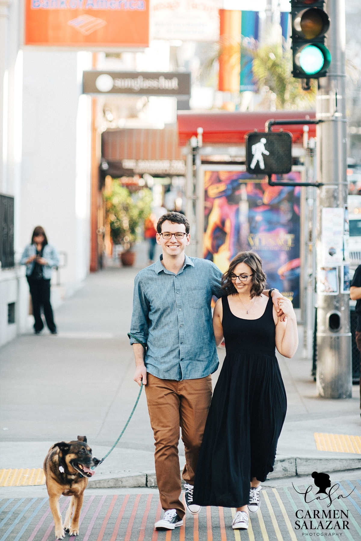 Smiling couple walking dog in the Castro District engagement session