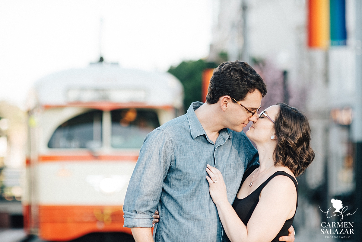 Couple kissing in Castro district in front of trolley by San Francisco wedding photographer Carmen Salazar