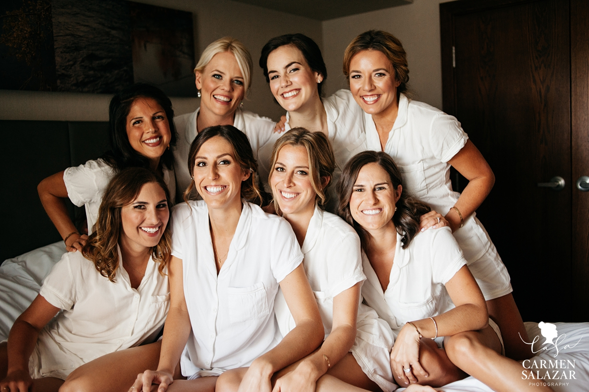 Smiling bride with bridesmaids in white pajamas