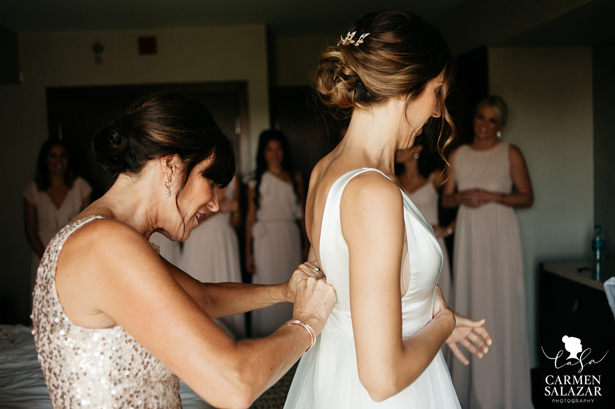 Bride getting into wedding dress with mother of bride by Sacramento Wedding Photographer Carmen Salazar