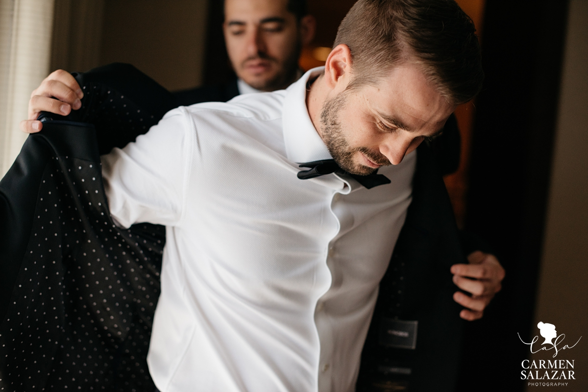 groom putting on black suit jacket with groomsman at Hilton Sacramento by Sacramento Wedding Photographer Carmen Salazar