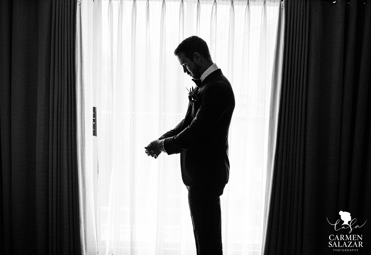 black and white picture of groom in window by Sacramento wedding photographer Carmen Salazar