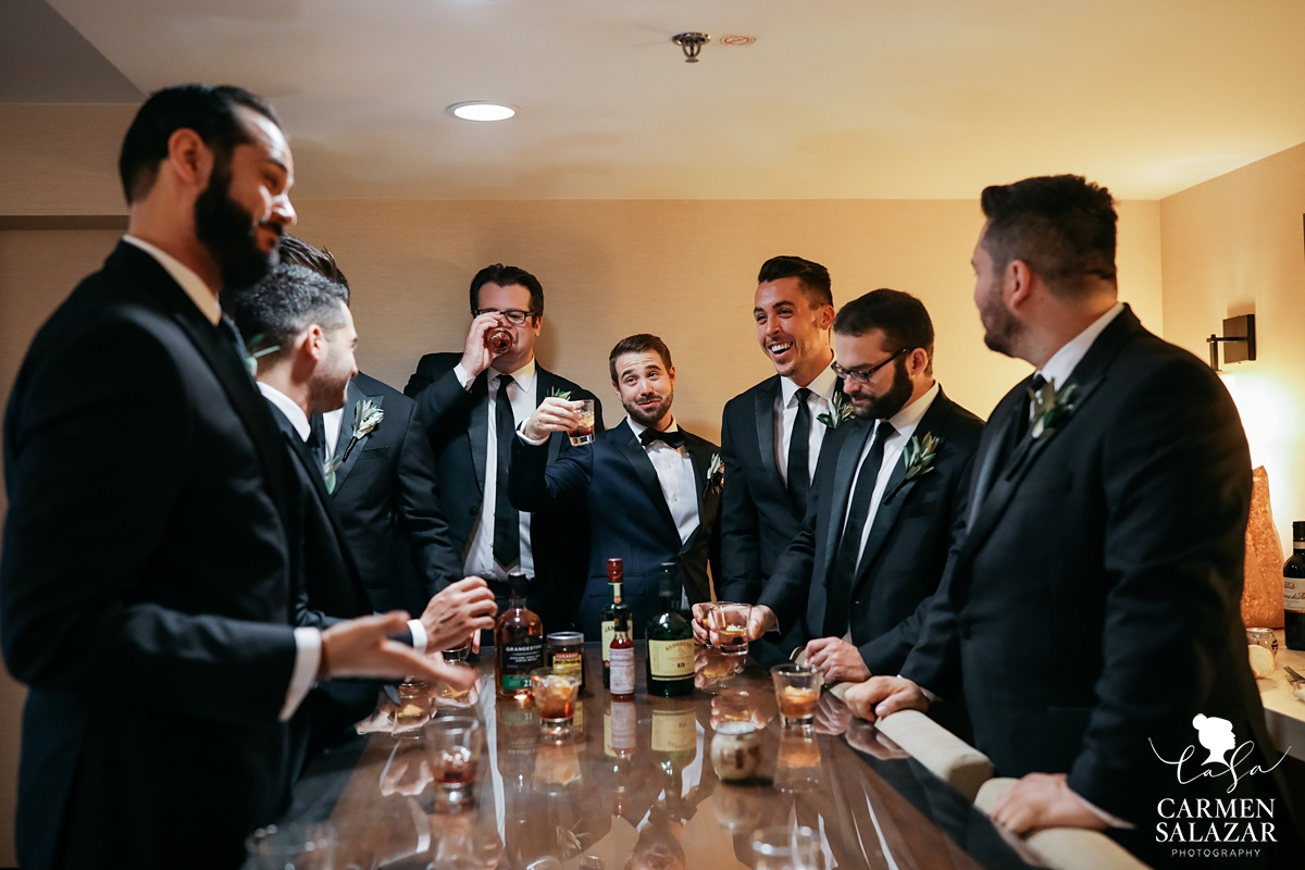 Groomsmen lined up around a bar table drinking whiskey in black suits at Hilton Sacramento by Sacramento Wedding Photographer Carmen Salazar
