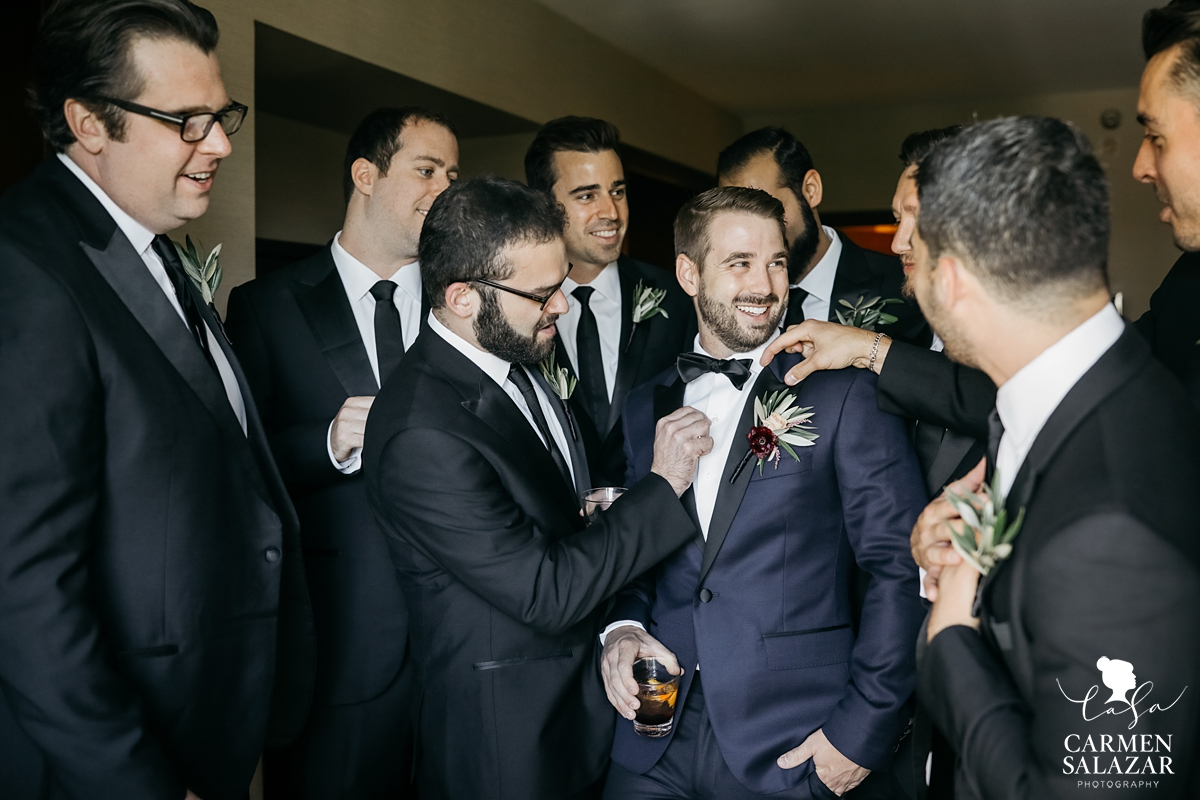 Smiling groom with whiskey surrounded by groomsmen at Hilton Sacramento by Sacramento wedding photographer Carmen Salazar
