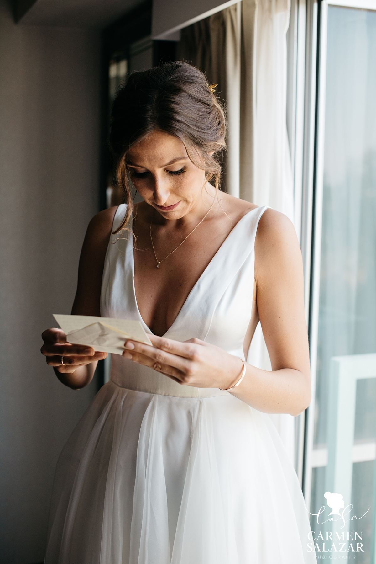 Bride in Sarah Seven gown reading a letter from groom in window light by Sacramento Wedding Photographer Carmen Salazar