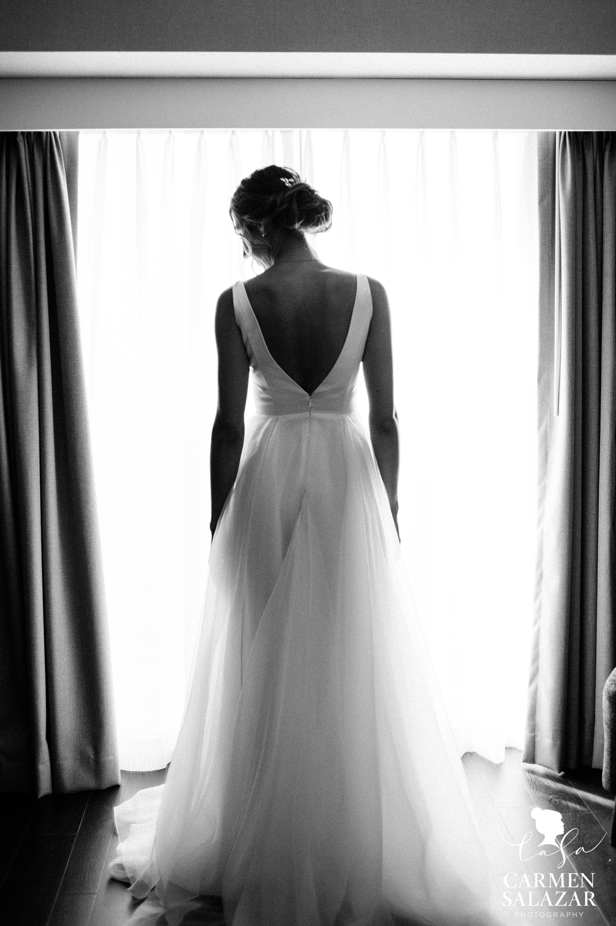 black and white picture of bride in Deep V wedding dress in front of window by Sacramento wedding photographer Carmen Salazar