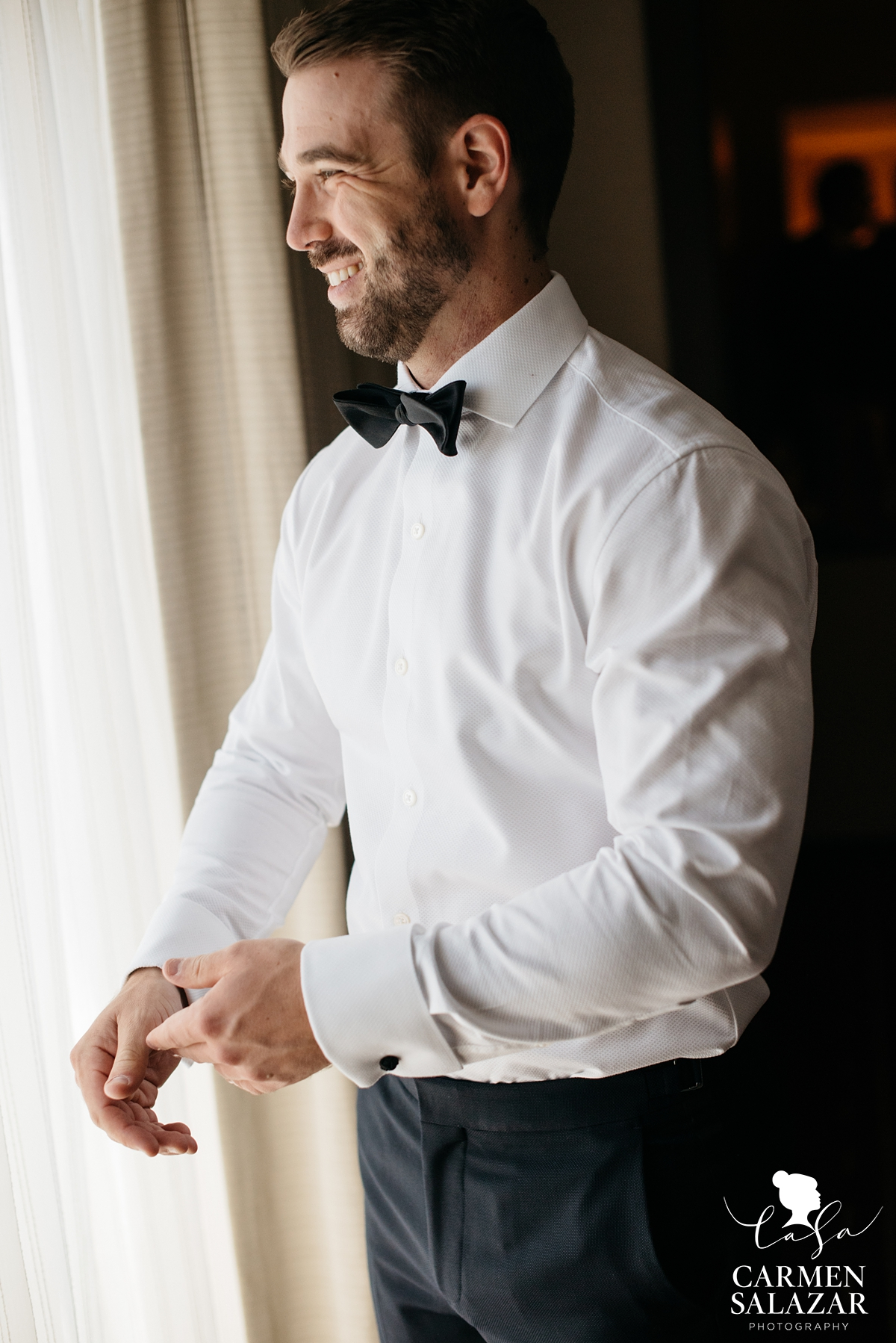 smiling groom in wedding suit fixing cufflinks and smiling by Sacramento wedding photographer Carmen Salazar