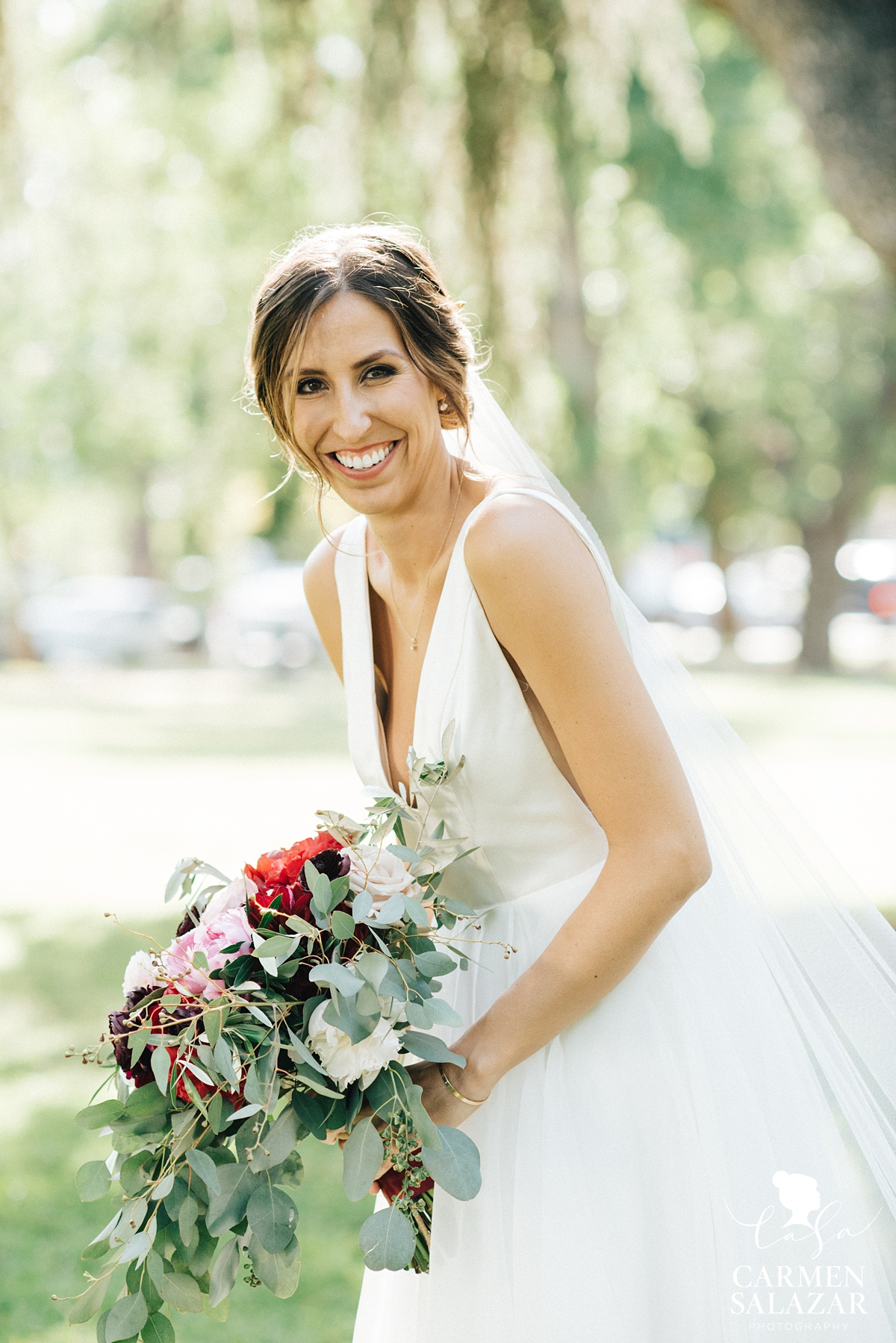 Laughing bride in Sarah Seven wedding gown with bouquet by Sacramento Wedding Photographer Carmen Salazar