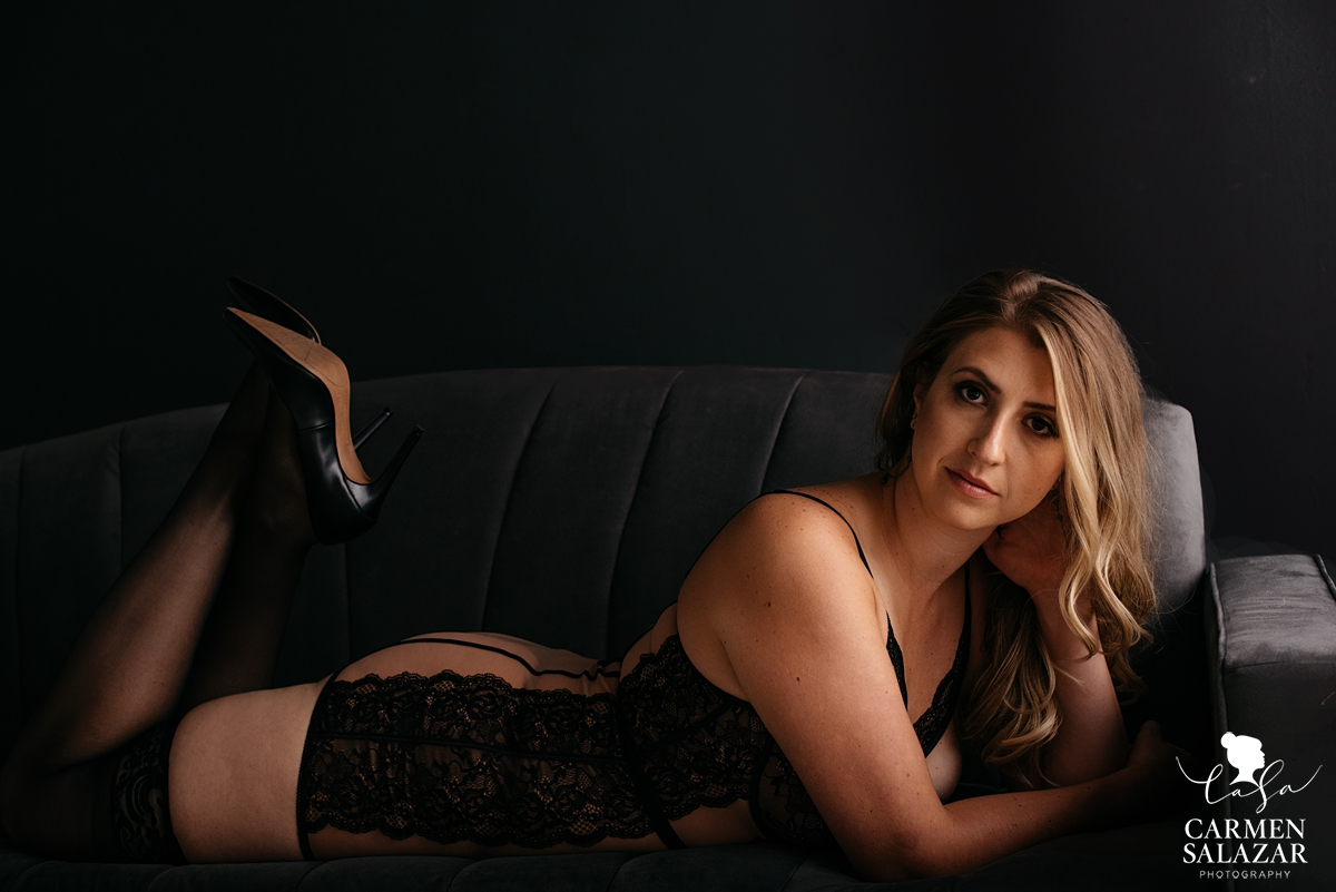 classy black lingerie shot of curvy woman on black couch with stilettos