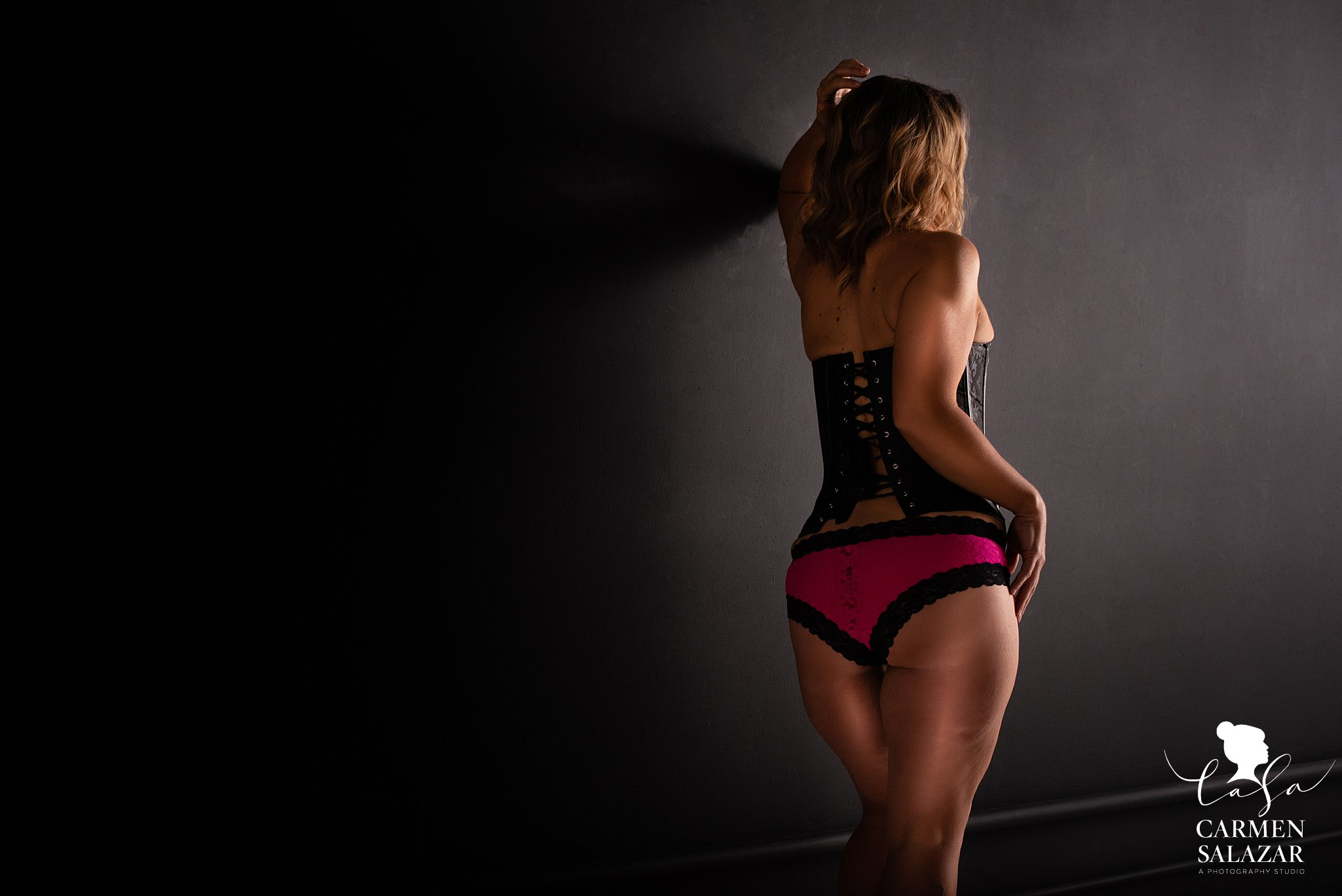 Moody and dark boudoir photo of a woman with pink panties