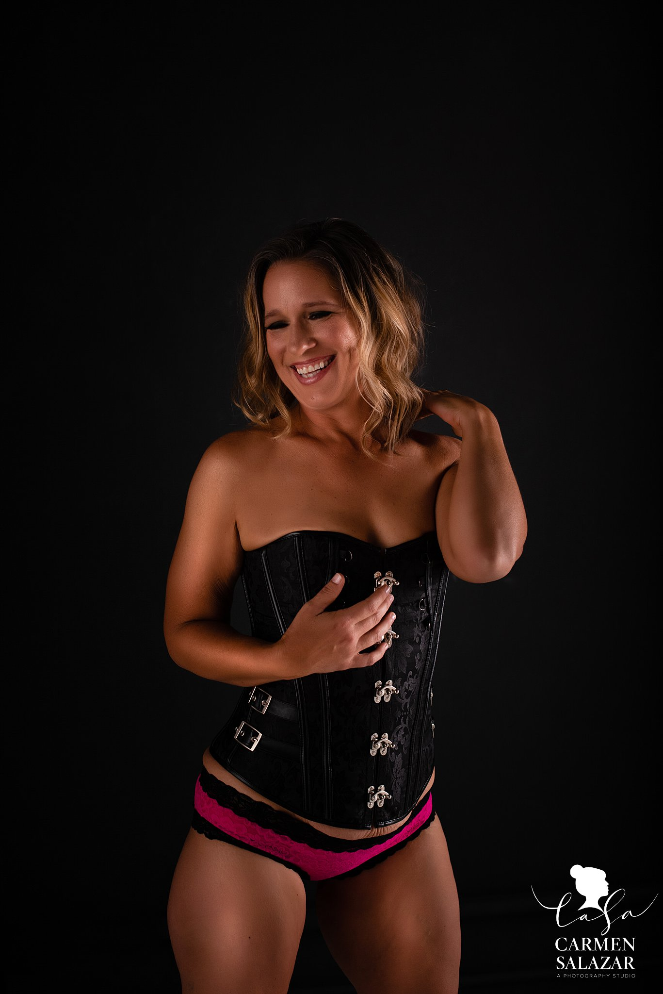 Smiling, sexy photo of woman in black corset