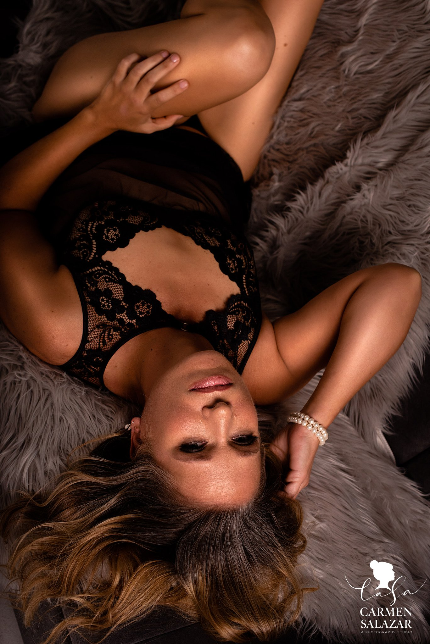 Seductive boudoir photo of woman in black lace bodysuit