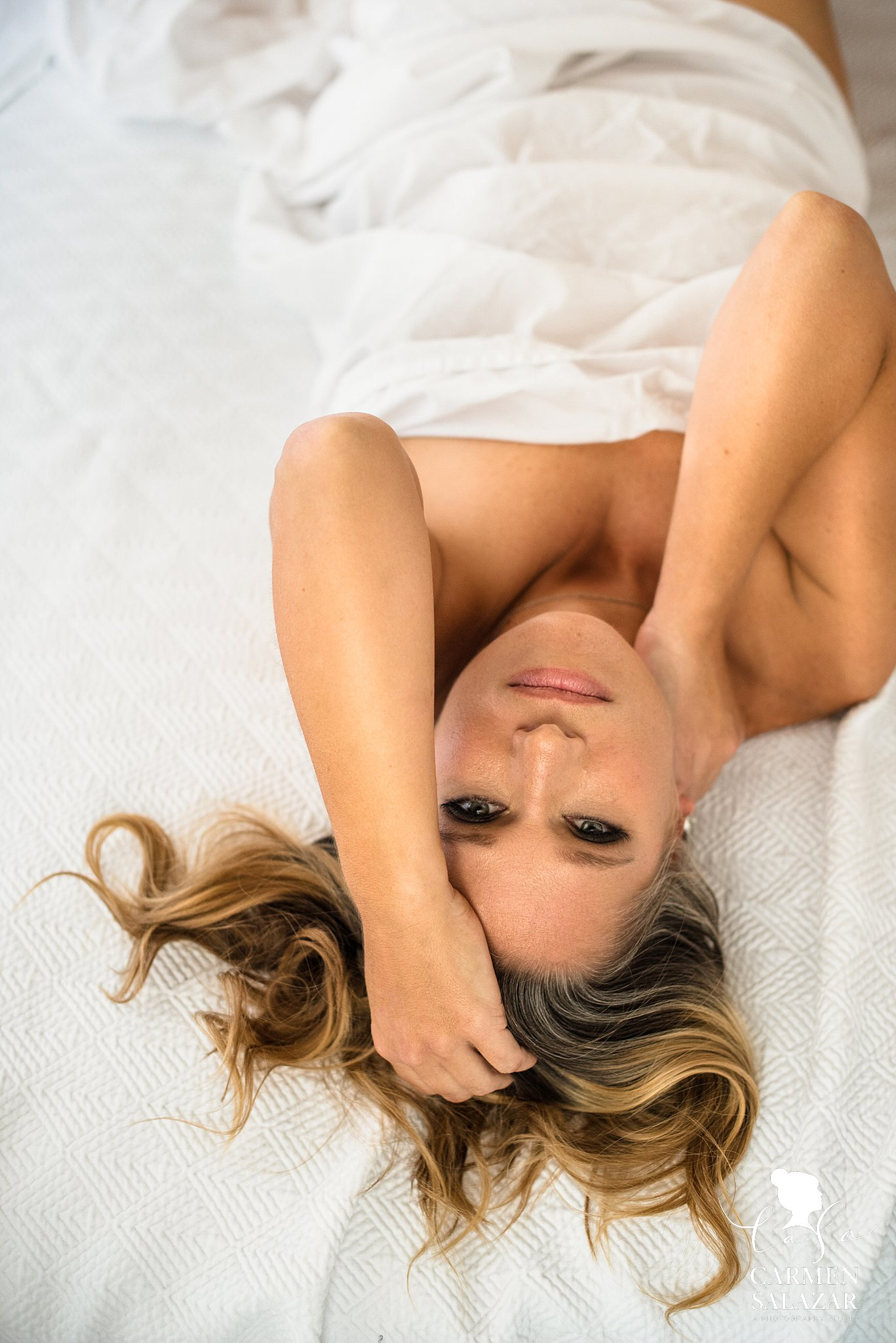 Beautiful natural light boudoir photo of a woman on a white sheet