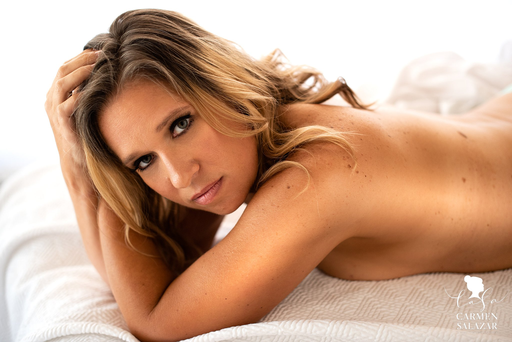Nude boudoir photo of a woman on bed with natural light