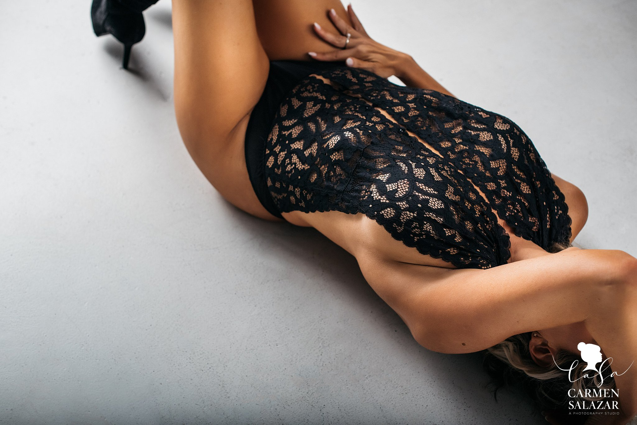 Boudoir picture of girl in lace bodysuit on the floorv by Sacramento Boudoir photographer Carmen Salazar